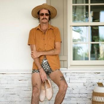 "The Dandy in burnt sienna Tropez Terry Cloth shirt and floral Gardenia-print ""Cassis Square Cut"" swim briefs. (Source: @eldandydelmar)"