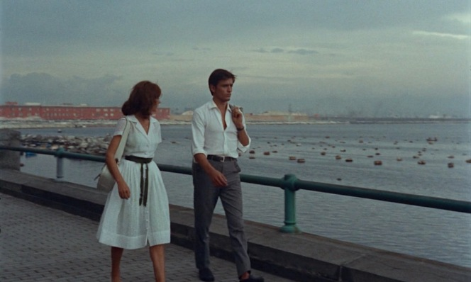 Marie Laforêt and Alain Delon stroll along Via Nazario Sauro against the Gulf of Naples.