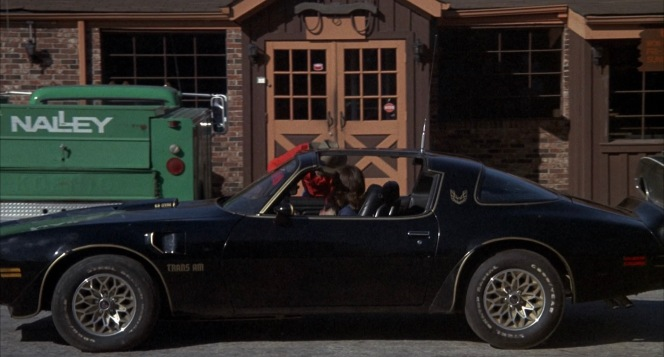 """Frog picks up the Bandit in his own Trans Am outside the """"choke and puke"""" where Sheriff Justice is wolfing down his diablo sandwich."""
