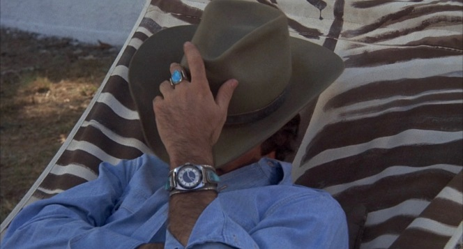 The Bandit flashes his turquoise ring and watch as he adjusts his hat to steal an amused peek at the Burdettes.