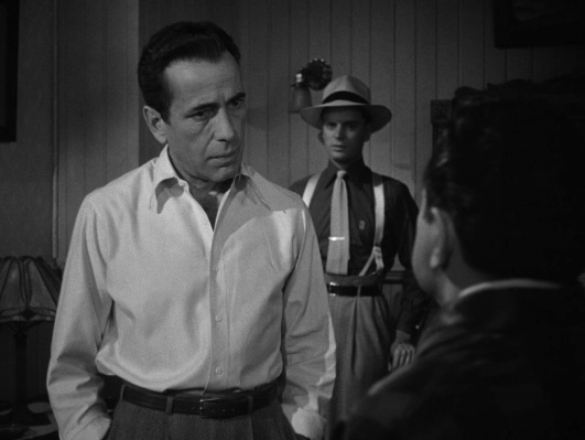 "Note how subtle Frank's plain white shirt looks when compared to Toots over his left shoulder, sporting monogrammed dark silk shirt, contrasting light knitted tie tucked into his ""Hollywood"" trousers supported by belt and braces, not to mention that wide-brimmed Panama hat or his spectator wingtips."