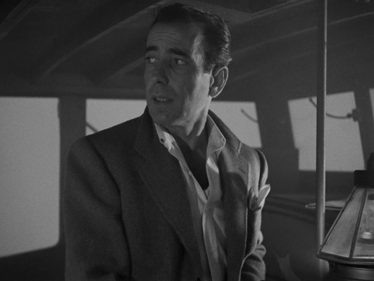 Bogie in his natural habitat: at the helm of a fishing boat.