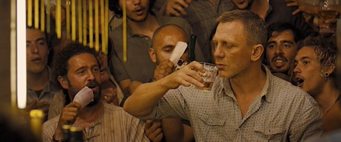 Clad in Zara shirt, James Bond (Daniel Craig) eyes a scorpion as he owns up to a bar challenge to down a dram of Macallan and capture the deadly arachnid in the glass before it can bite him in Skyfall (2012).