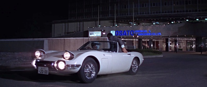 Aki spirits Bond away from the gunfight at the Osato building in her custom Toyota 2000GT roadster.