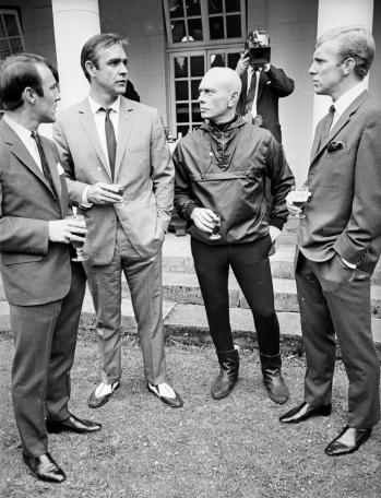 Sean Connery loosens his tie for a drink with Jimmy Greaves, Yul Brynner, and Bobby Moore when they visit Pinewood Studios during the production of You Only Live Twice (1967). Photo sourced from thunderballs.org.