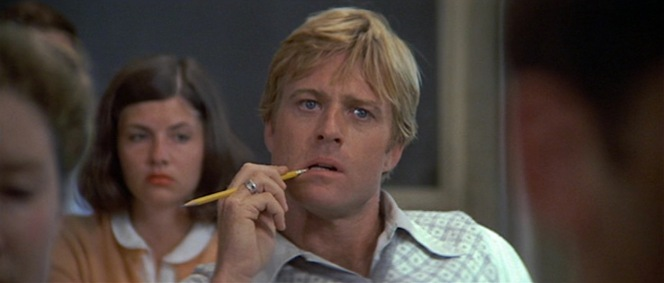 """Clad in what appears to be the same shirt but a different sweater, Hubbell nervously gnaws on his pencil as his story, """"The All-American Smile"""", is praised and read aloud by his writing professor."""