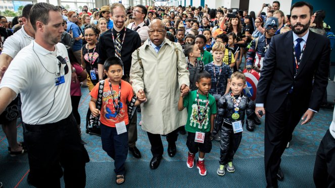 Dressed in a raincoat and knapsack similar to what he had worn during the 1965 Selma march, John Lewis is joined by his policy aide and co-author Andrew Aydin as they lead young Comic-Con attendees around the event. (Photo by Carlos Gonzalez for The New York Times)