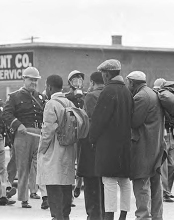 The real Lewis' famous backpack seen in detail in this photo by Tom Lankford for the Birmingham News, taken when Lewis, Williams, Bob Mants, and Albert Turner were confronted by Major John Cloud of the Alabama Highway Patrol moments before violence against the demonstrators ensued on March 7, 1965.