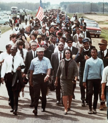 The Kings and John Lewis lead the marchers out of Selma on March 21, 1965. Note how neatly the actual figures' wardrobe matches Ruth E. Carter's costume design, with the minor exception of the cinematic Lewis wearing a white tab-collar shirt and tie as opposed to the pale blue button-down seen in real life.